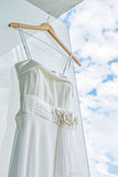 Weißes Hochzeitskleid auf Front der hellen Wand Lizenzfreie Stockfotos