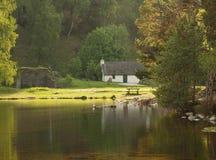 Weißes Häuschen auf See, Schottland Lizenzfreie Stockfotografie