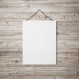 Weißes leeres Plakat, das am Ledergürtel auf hölzernem Hintergrund hängt Lizenzfreie Stockfotos