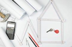 Weißes Meterwerkzeug, das ein Haus bildet und Werkzeuge auf Weiß ausführt Lizenzfreie Stockfotografie
