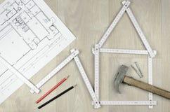 Weißes Meterwerkzeug, das ein Haus bildet und Werkzeuge auf woode ausführt Stockfoto