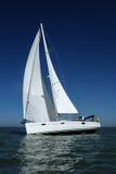 Weißes Segelboot, das Geschwindigkeit unter blauem Himmel nimmt Lizenzfreies Stockfoto