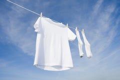 Weißes T-Shirt und Socken auf blauem Himmel Lizenzfreies Stockbild