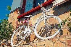 Weißes Weinlesefahrrad mit roten Blumen Lizenzfreie Stockfotografie