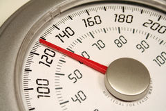 Weigh In. A close up of a weight scale set at 128 Stock Image