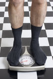 Weigh-in. Closeup of a man standing in his socks on a scale Stock Photos