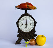Weigh fruits and vegetables. Weighing scales with an old cast-iron tomatoes,a carrot,an onion and an apple Stock Photos