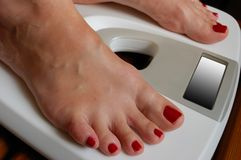 Weigher. And white female feet Stock Images