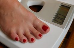 Weigher. White weigher and  female foot Royalty Free Stock Photography
