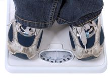 Weighing. Feet in sport shoes on bath scale Stock Images