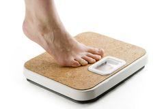 Weighing In. A female foot standing on tip toe, on a bathroom scale stock images
