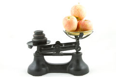 Weighing apples. An old weighing scales painted black with a brass bowl containing apples all isolated on white Stock Images