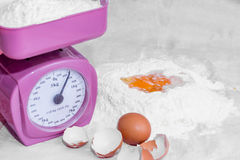 Weighing flour on a kitchen scale Royalty Free Stock Image