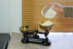 Weighing flour in scales Royalty Free Stock Images