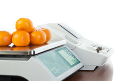 Weighing of fruits on electronic scales. On white background Royalty Free Stock Photo