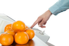 Weighing of fruits on electronic scales Royalty Free Stock Photos