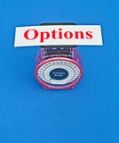 Weighing the options. Text 'options' in red letters on white card placed on top of small weighing scale, giving concept of weighing options, blue background Royalty Free Stock Photography