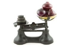 Weighing red onions. An old weighing scales painted black with a brass bowl containing red onions all isolated on white Stock Photos