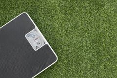 Weighing scale on green grass royalty free stock photo