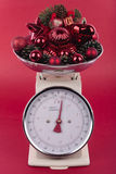 Weighing scales with decorations. Weighing scales with christmas decorations isolated on red Stock Photos