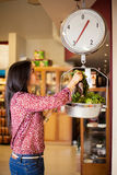 Weighing some vegetables. Beautiful girl weighing some vegetables on a scale at the grocery store Royalty Free Stock Photo