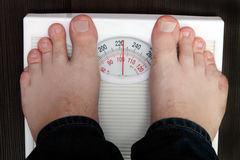 Weighing. The young man is weighed on scales stock photo