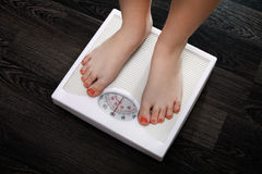 Weighing. The young woman is weighed on scales stock photos
