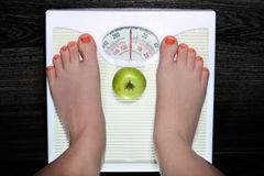 Weighing. The young woman is weighed on scales royalty free stock images