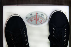 Weighing. The young woman is weighed on scales royalty free stock photo