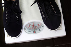 Weighing. The young woman is weighed on scales royalty free stock image