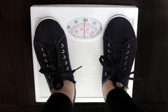 Weighing. The young woman is weighed on scales stock images
