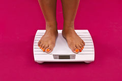 Weight. A woman checks on the scales of their weight Royalty Free Stock Photography