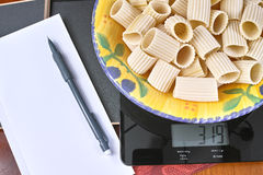 Weight control - black glass kitchen scale with Italian pasta, pencil and paper. Diet, weight lose, self-control, discipline Royalty Free Stock Image