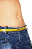 Weight control concept. Woman belly with measuring tape as a belt, isolated on white background royalty free stock photography