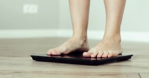 Barefooted woman is standing on scales weightning at home in room, feet closeup. Weight control and healthy lifstyle concept. Barefooted woman is standing on stock video