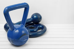 Weight, dumbbell and kettlebell on a white wooden floor. Kettlebell, weight and blue dumbbell on a white wooden floor Stock Image