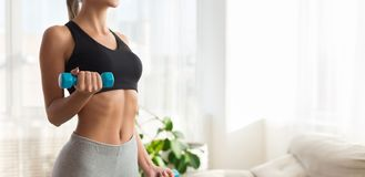 Unrecognizable fitness woman exercising with dumbbells, copy space. Weight exercise. Slim girl exercising with dumbbells at home interior, copy space royalty free stock photos