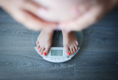 Weight gain during pregnancy. Concept with pregnant woman on weight scale Stock Photos