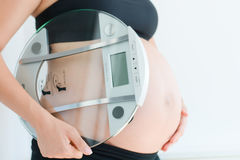 Weight gain during pregnancy with pregnant woman holding scale. Weight gain during pregnancy with pregnant woman holding glass made weighing scale Stock Photo
