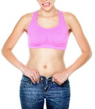 Weight gain and weight loss woman buttoning pants. With difficulties. Jeans too tight on female waist. Woman making funny face expression isolated on white Stock Photo