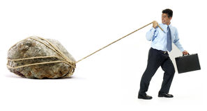 The weight of the hard work. Businessman pulling a big rock on white background Royalty Free Stock Photos