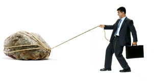 The weight of the hard work. Businessman pulling a big rock on white background Royalty Free Stock Photo
