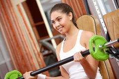 Weight lifting. Photo of active girl lifting dumbbell - building muscle stock photo