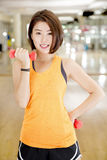 Weight lifting. An Asian lady doing weight lifting exercise in a gym Royalty Free Stock Photos