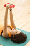Weight lifting. An Asian lady laying down doing weight lifting exercise in a gym Royalty Free Stock Photos