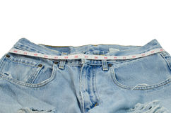 Weight lose. Measuring tape on Jeans pants stock image
