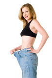 Weight loss. Attractive slim blond woman demonstrating weight loss by wearing an old pair of jeans and holding out to show how big the pants are royalty free stock image