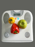 Weight Loss. Apple, red pepper and tomato on a fat analyser scale, symbolizing diet choices for a healthy lifestyle Royalty Free Stock Photography