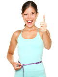 Weight loss. Woman smiling happy excited standing with measuring tape giving thumbs up success hand sign isolated on white background. Asian female fitness Stock Photo