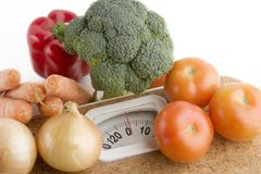 Weight Loss. Garden vegetables on a bathroom scale Royalty Free Stock Photo